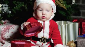 Baby in Santa suit, Santa Claus little boy, child sits in the carnival costumes, Christmas costumes under the Christmas stock video