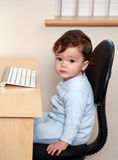 Baby sat at desk Royalty Free Stock Images