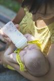 Baby saugt auf einer Flasche Lizenzfreie Stockfotografie