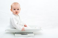 Baby on scales Royalty Free Stock Image