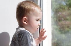 Baby schaut aus Fenster heraus Lizenzfreie Stockbilder