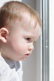 Baby schaut aus Fenster heraus Lizenzfreie Stockfotos