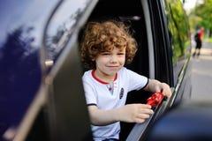 Baby schaut heraus das Autofenster Stockfoto