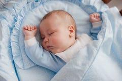 Baby schläft mit einer Wiege Stockbild