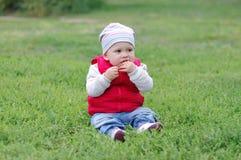 Baby schmeckt den wilden Apfel, der auf Gras sitzt Lizenzfreie Stockfotografie