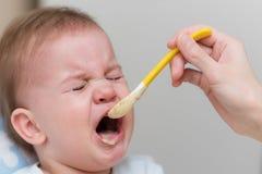 Baby schreit und lehnt ab, Gemüsepüree zu essen Stockfotografie