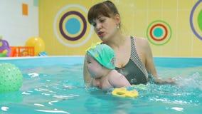 Baby-Schwimmen mit Trainer im Planschbecken stock video footage