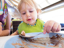 Baby scraping bowl with spoon Stock Photography