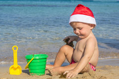 Baby by the sea in a cap of Santa Claus Royalty Free Stock Images
