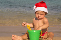 Baby by the sea in a cap of Santa Claus Stock Photography