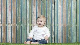 Baby seated on grass in front of a fence Stock Photography