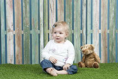 Baby seated on grass in front of a fence Royalty Free Stock Image