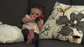 Baby Seated Playing With Toys. A great baby sitting up and playing with some toys stock footage