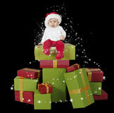 Baby seated on a stack of christmas presents. Black background royalty free stock photography