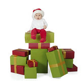 Baby seated on a stack of christmas presents. Isolated on white background Stock Images