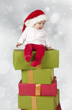 Baby seated on a stack of christmas presents. Bokeh background Stock Photos