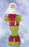 Baby seated on a stack of christmas presents. Blue bokeh background royalty free stock photos