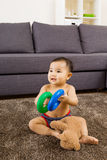 Baby seating on carpet and play doll Stock Images