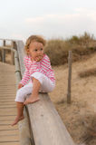 Baby is seatting on the bridge and looking ocean Stock Image
