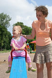 Baby  on seesaw with mother Stock Images