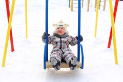 Baby on seesaw in winter Stock Image