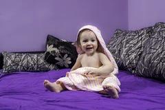 Baby ser den bärande handduken på ett vänstert Royaltyfri Foto