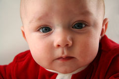 Baby with Serious Facial Expression. Cute Baby with Serious Facial Expression and Red Outfit royalty free stock images