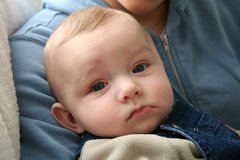 Baby with Serious Facial Expression. Cute Baby with Serious Facial Expression Being Held by his Mother stock image