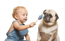 Baby Sharing. A baby shares his lollipop with a puppy Royalty Free Stock Photo