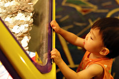 Baby and shining coins. A little baby girl looking curiously at coins in casino Stock Image
