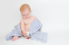 Baby in a shirt reaching for his pacifier. Chubby babe in a plaid shirt sitting on the floor and reaching for his pacifier royalty free stock images