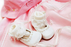 Baby shoes. White baby shoes and socks lying on pink dress Stock Images