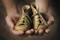 Baby Shoes. Man holding a pair of old baby shoes royalty free stock images