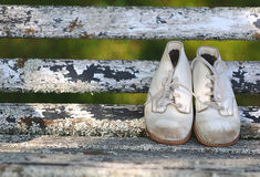 Baby Shoes. Scuffed old fashioned vintage baby shoes on a weathered bench Stock Images