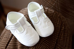 Baby shoes. White baby shoes for baptism stock photo