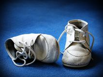 Baby shoes. Pair of old tiny baby shoes on blue background. With copyspace Stock Photography