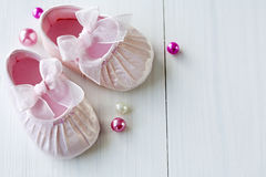 Baby shoes. Satin pink baby shoes on wooden floor, room for text, the floor-line is easily removed for a different cleaner look royalty free stock photos