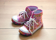 Baby shoes. Pink baby shoes on wooden background Stock Photo