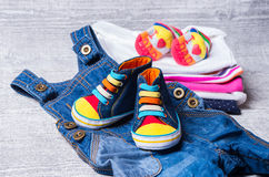 Baby shoes for babies and a set of clothes. In the background Stock Photos