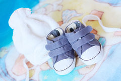 Baby shoes and baby cap. Baby blue shoes and baby white cap Stock Photography