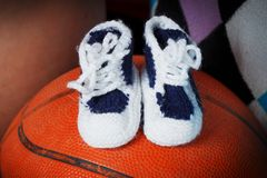Baby shoes are on a basket ball royalty free stock photo