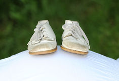 Baby Shoes on belly. Vintage baby shoes balancing on pregnant belly. Exterior Royalty Free Stock Image