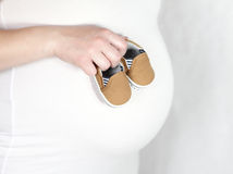 Baby shoes on belly Stock Photography