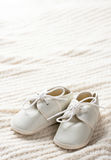 Baby shoes and blanket. White baby shoes sitting on baby blanket with copy space Royalty Free Stock Photography