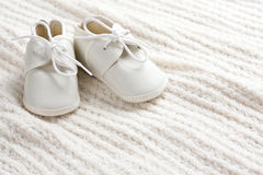 Baby shoes and blanket. A pair of baby shoes sitting on baby blanket with copy space stock photography