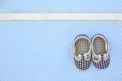 Baby shoes on blue polka Stock Photography