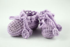 Baby shoes. Close up of hand-knitted baby shoes on white background Royalty Free Stock Photography