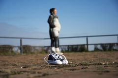 Baby shoes close up with pregnant woman behind in a blur Stock Images