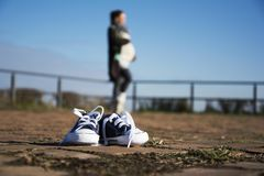 Baby shoes close up with pregnant woman behind in a blur Royalty Free Stock Image