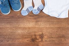 Baby shoes and clothing for newborn, expecting for kids concept, place for text. Baby shoes and clothing for newborn, expecting for kids and extending family stock image